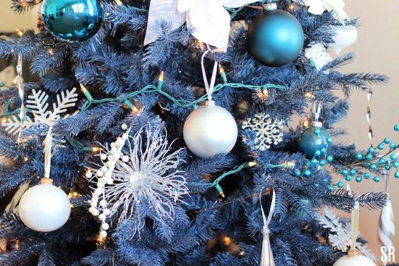 a blue Christmas tree with silver and white decorations