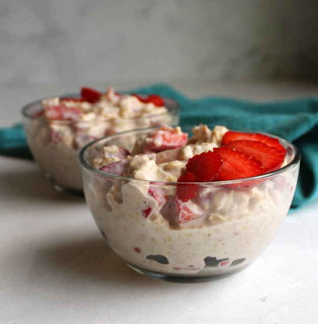 two small glass bowls full of strawberries and cream overnight oatmeal with fresh strawberries on top