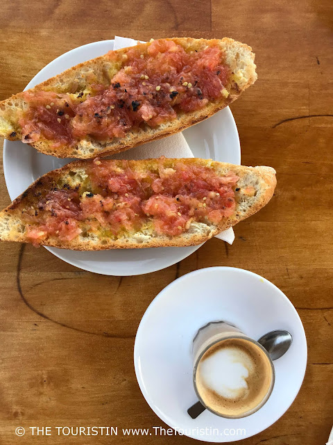 Two slices of toasted bread with grated tomatoes on a white plate next to a cup of coffee.