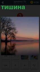 Наступили сумерки и в тишине стоит одинокое дерево на берегу реки с легкой дымкой вдали
