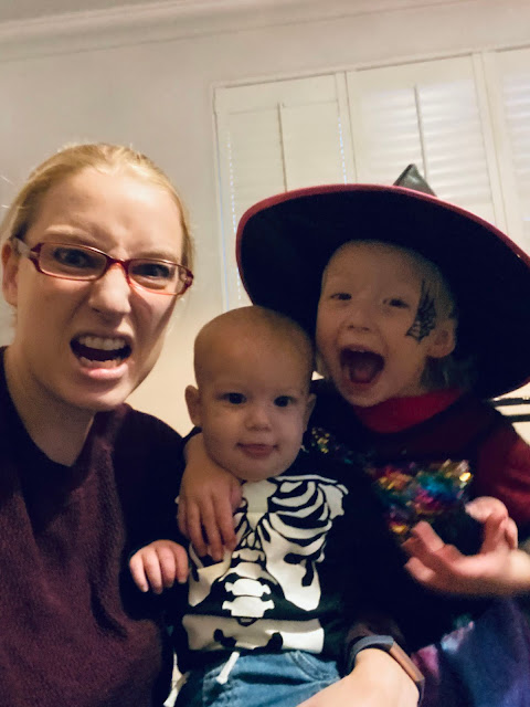Me and my younger 2 children getting in the halloween spirit by pulling faces. The girl is wearing a witches outfit and the baby boy a t-shirt with a skeleton print