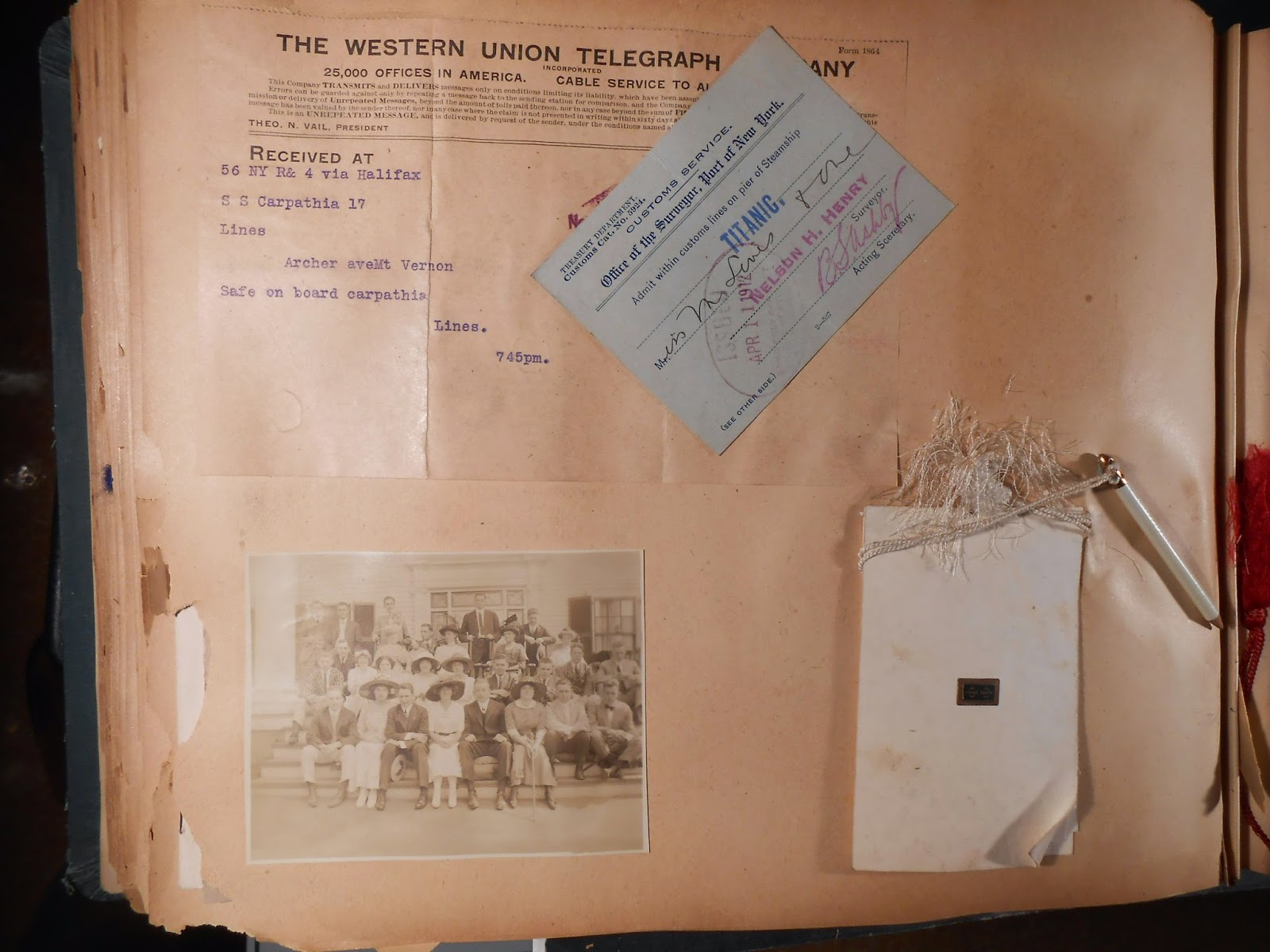 A photograph from inside a scrapbook, including a ticket for the Titanic and a telegram announcing safety.