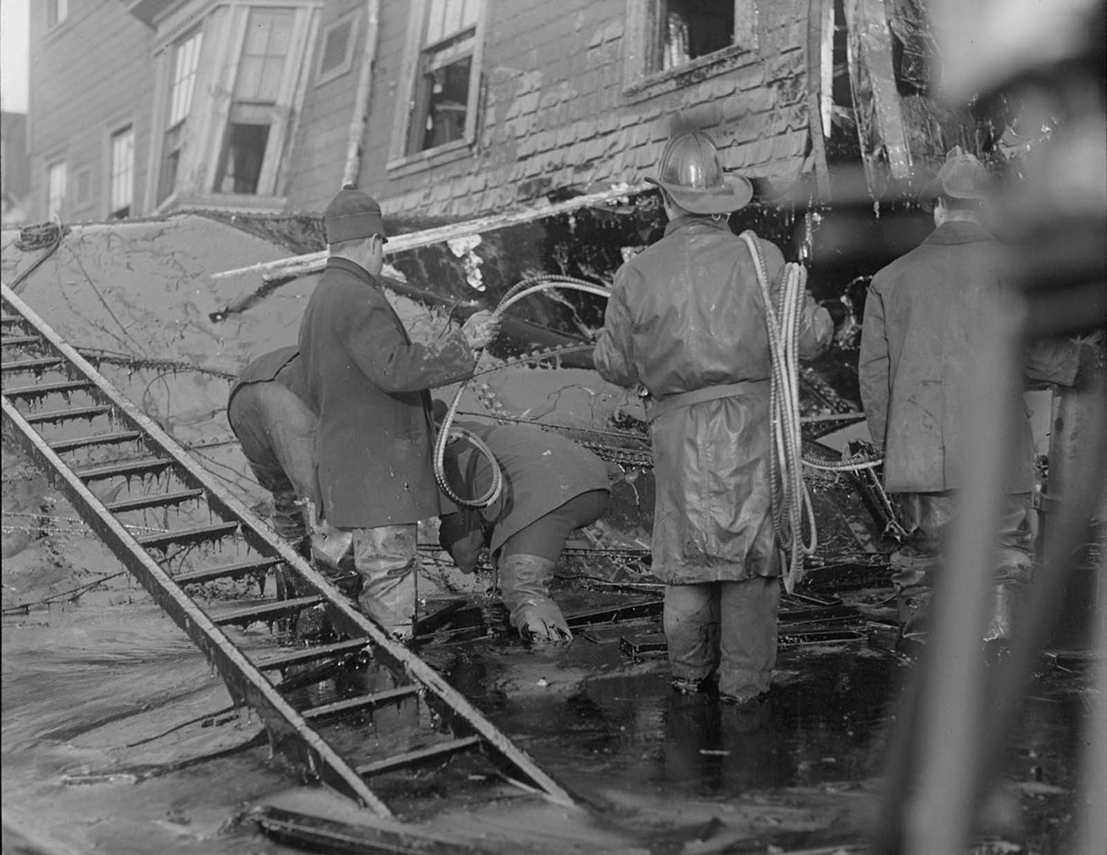 Firemen standing in thick molasses after the disaster. Muck drips off the ladder's rungs.