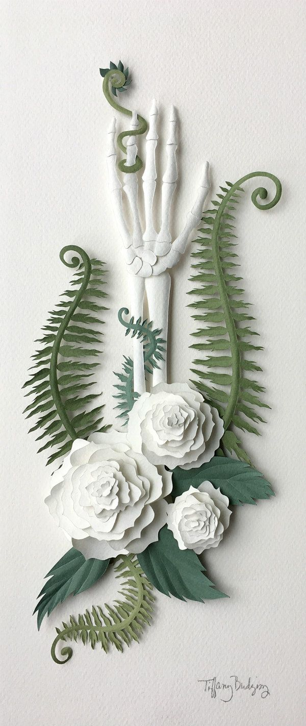 paper sculpture skeleton arm surrounded by white flowers and green ferns