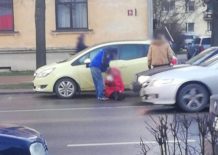 Vīrieši palīdz cietušajai gājējai, kura atspiedusies pret vieglo auto sēž uz ceļa braucamās daļas