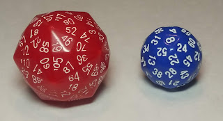 A large red die with so many faces it's little more than a sphere with a few pointy areas, with white numbers printed in a circle around each point, and a slightly smaller blue die with a series of white number on each face, which are diamond-shaped.