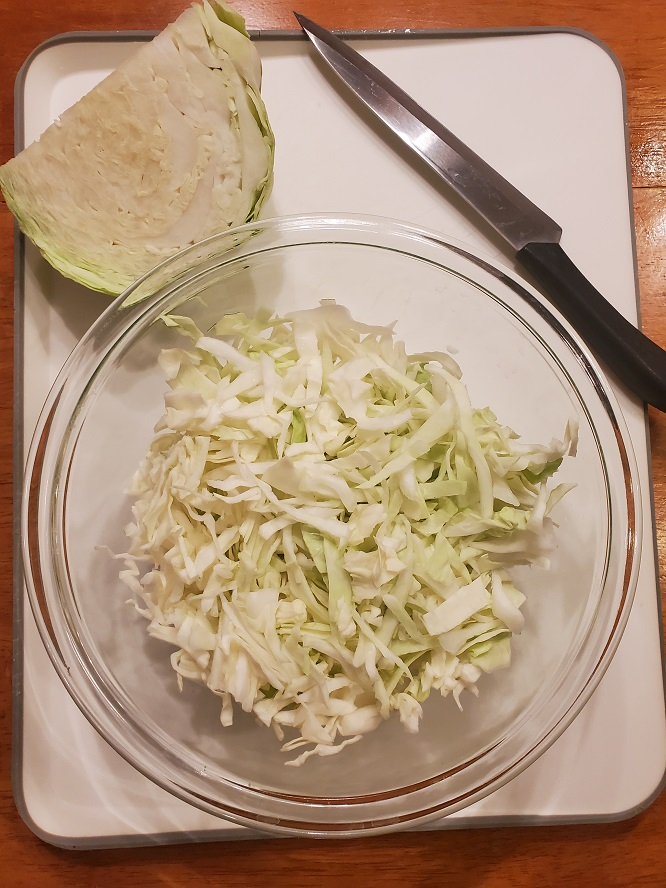 this is chopped shredded cabbage with a knife and cutting board
