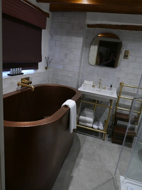 A bathroom containing an absolutely enormous oval copper bath.