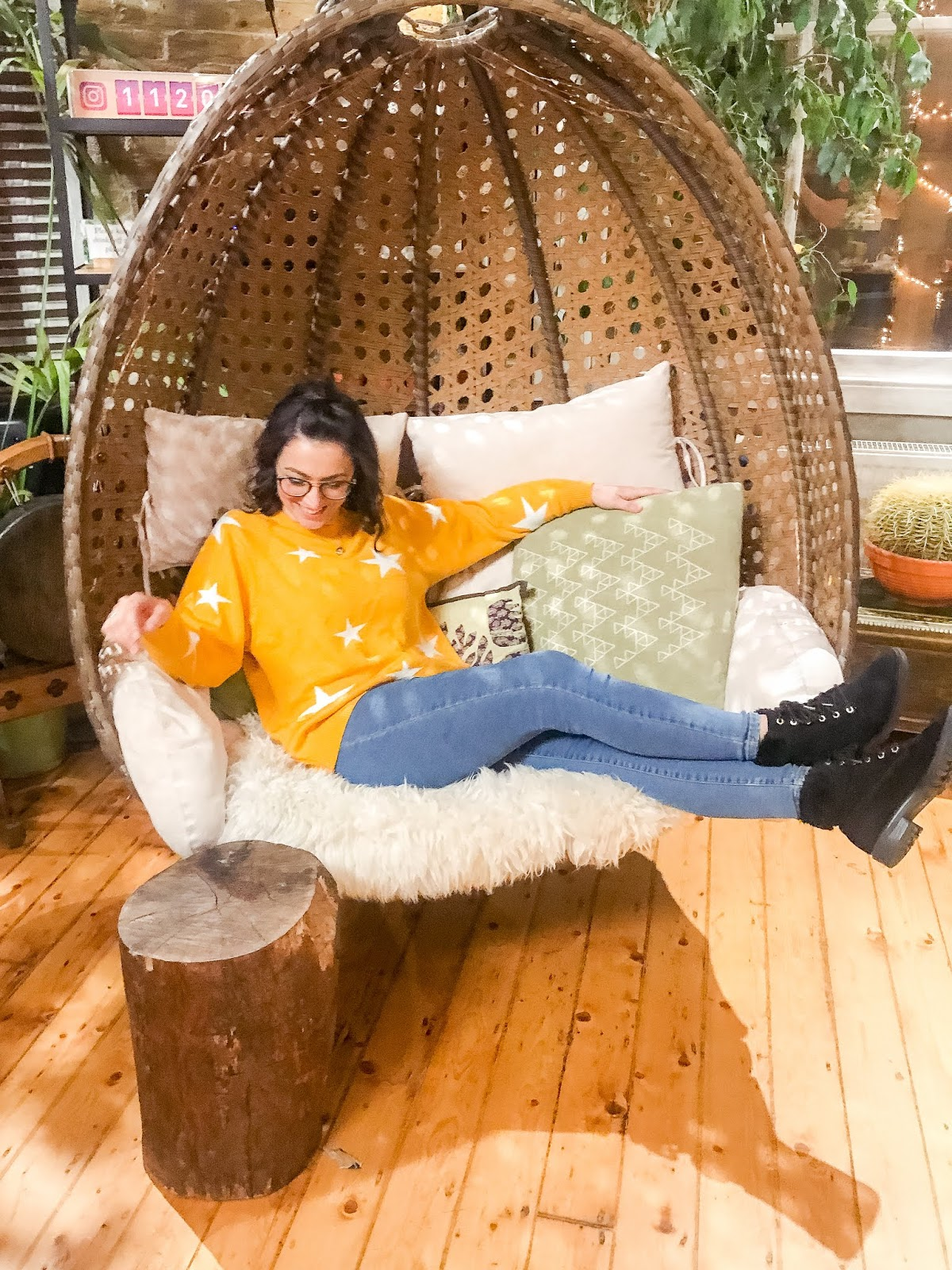 I'm sitting in a ceiling hung wicker basket chair laughing in a yellow with white stars jumper, blue jeans and black flat boots.