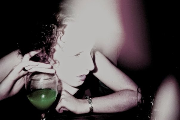 Much younger Sarah drinking a bright green cocktail