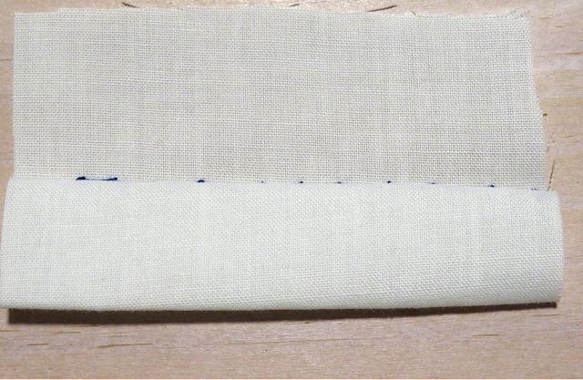 Puntada invisible con hilo azul sobre tela blanca por el revés