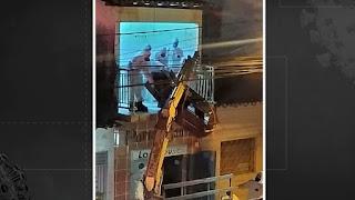 Corpo de homem em caixão é retirado de apartamento com auxílio de caminhão-guincho, na PB