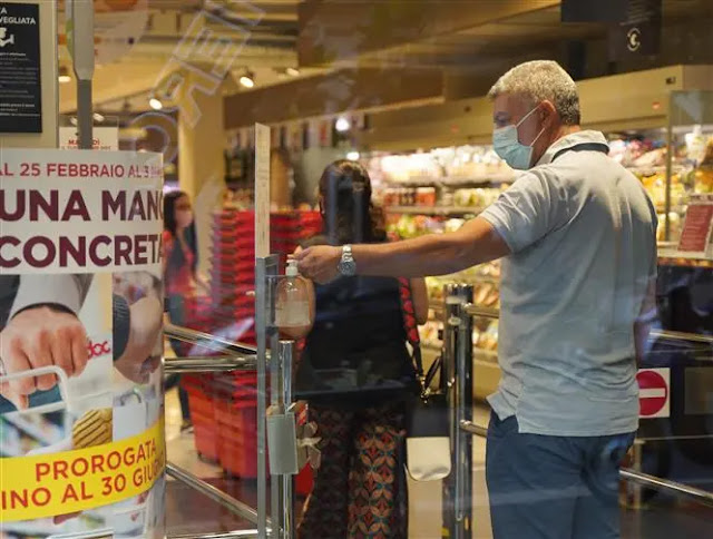 Customers disinfect their hands to prevent COVID-19 infection before entering a supermarket in Rome, Italy. Photo: THX