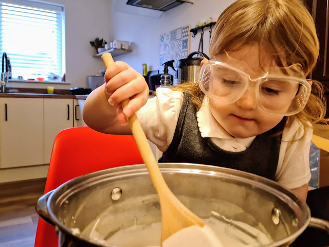 Image of a young girl in a school uniform wearing safety goggles over her eyes. She is sat on a red eames style chair and is mixing a white liquid (plaster of paris) inside a large metal stock pot with a wooden spoon.