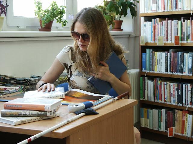 Linda v knihovně sedí u stolu. Na stole knihy, lupa, bílá hůl