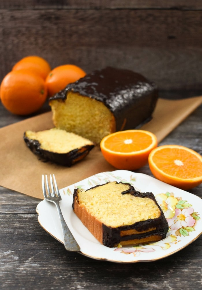A slice of jaffa orange cake sliced on a teaplate next to the whole cake