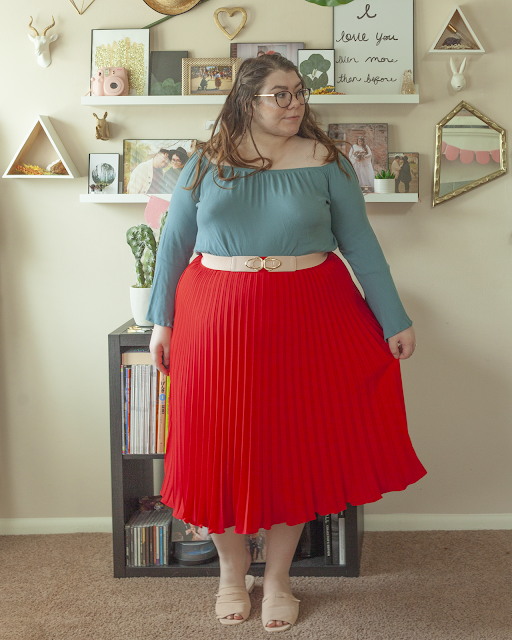 An outfit consisting of a Turkish blue off the shoulder blouse with angel sleeves tucked into a red pleated skirt belted with a pastel pink belt and pastel pink slide sandals.