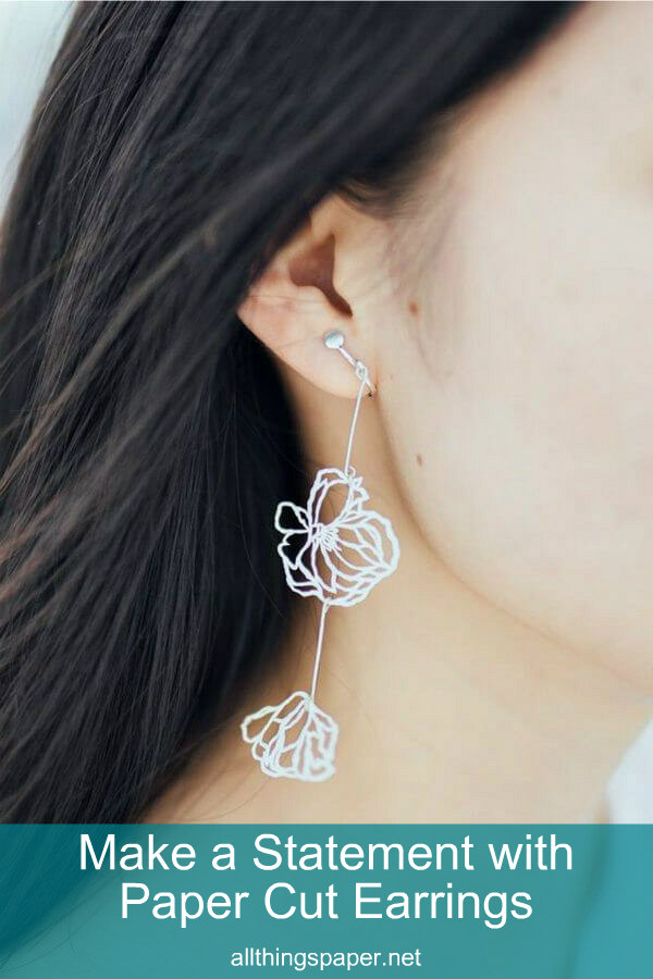 white drop earring with two papercut flowers on model