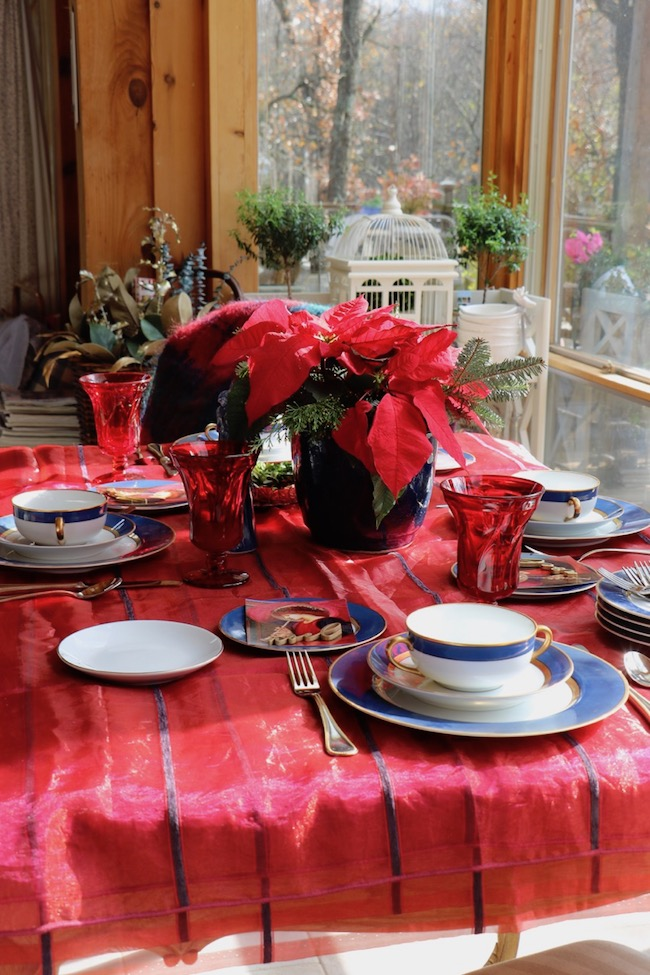 Red sheer, shimmering fabric with navy blue velvet stripes creates a festive tablecloth for a Christmas table setting