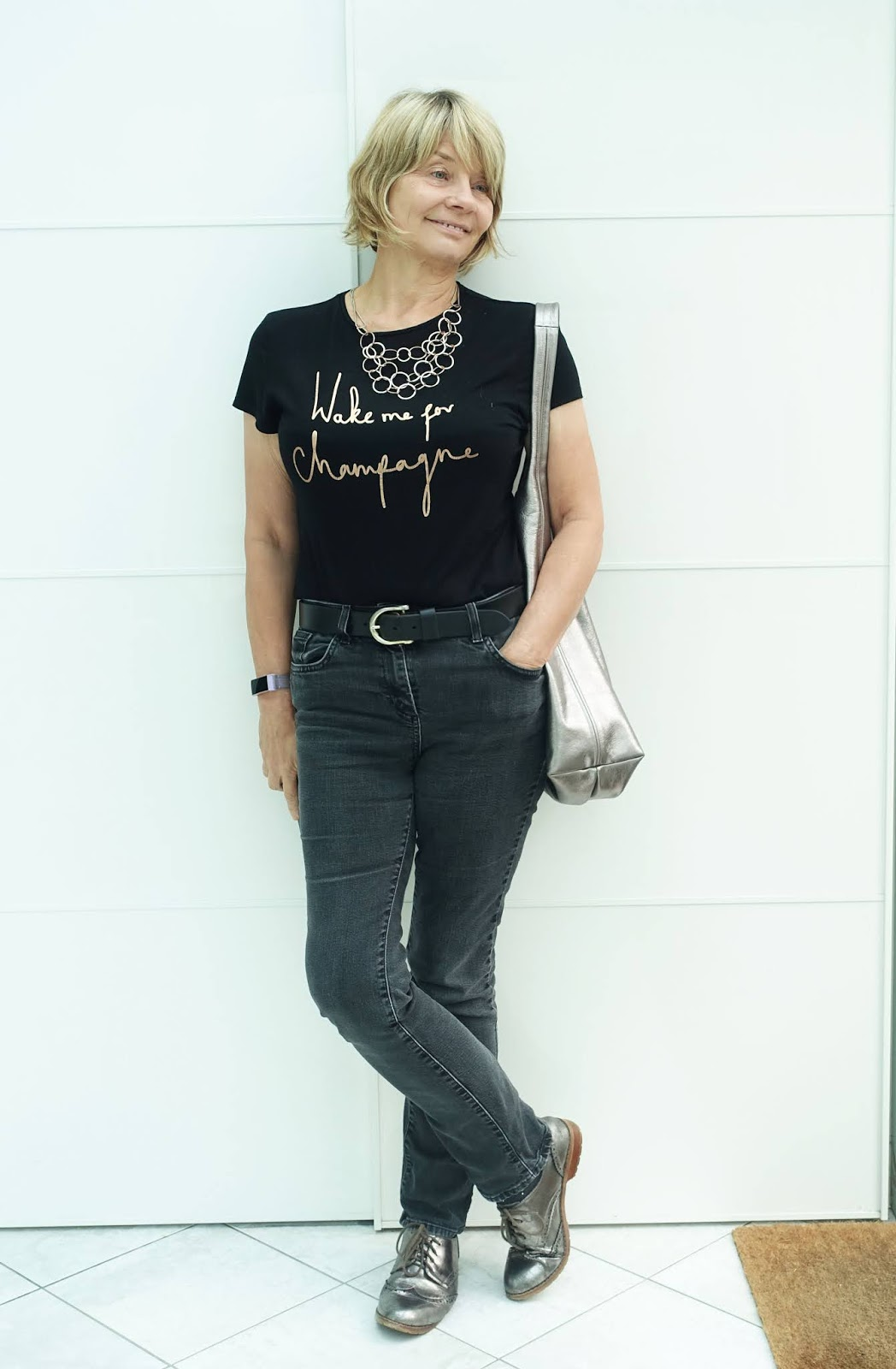 Over 50s woman in black jeans and slogan tee with metallic bag and brogues