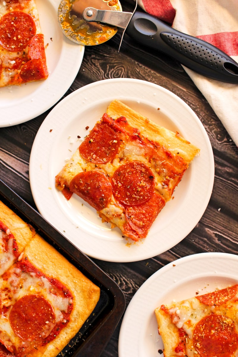 A square slice of pepperoni pizza with cresent roll crust on a white plate on a dark wood background.