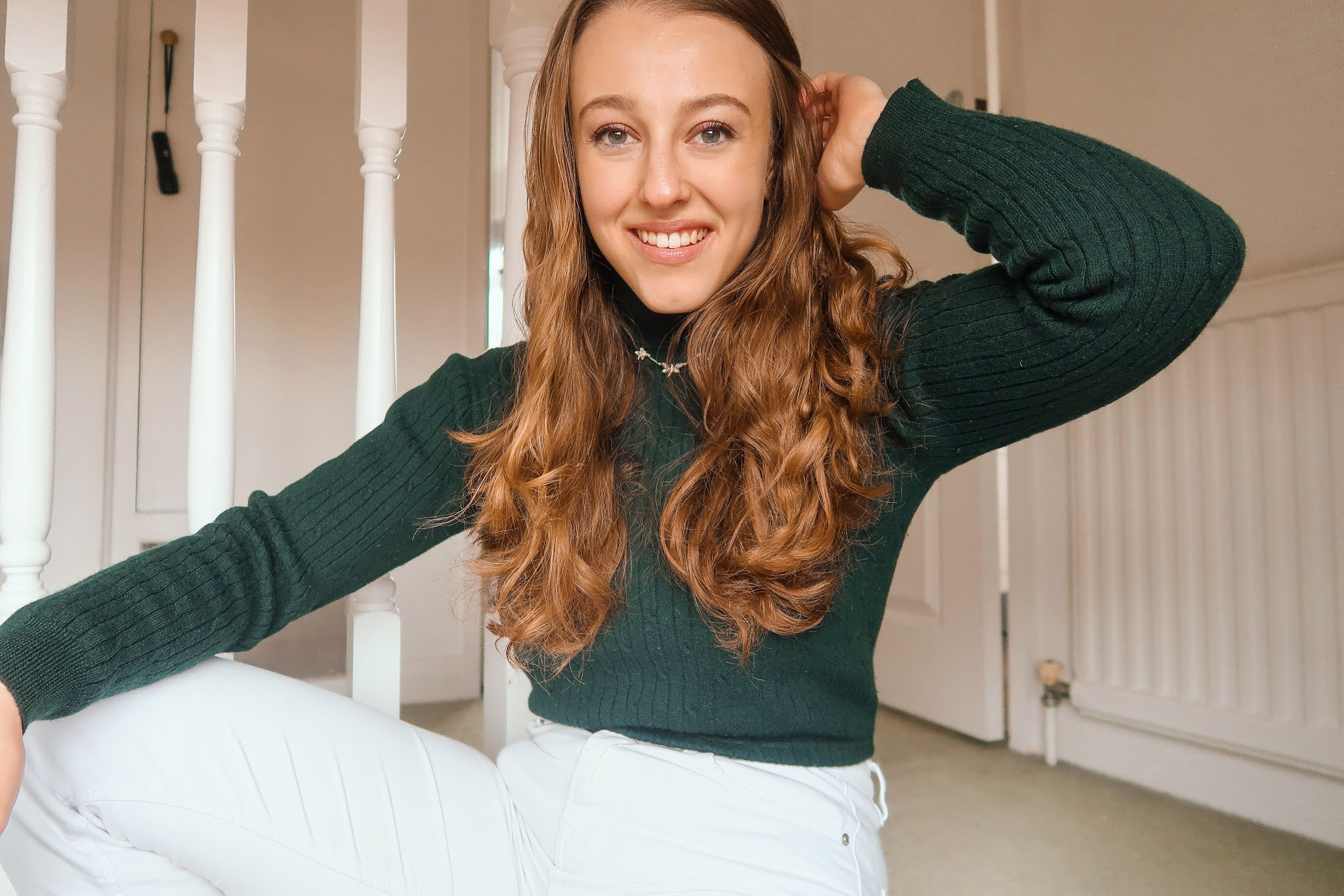 Georgie in her house wearing a green turtleneck and white jeans