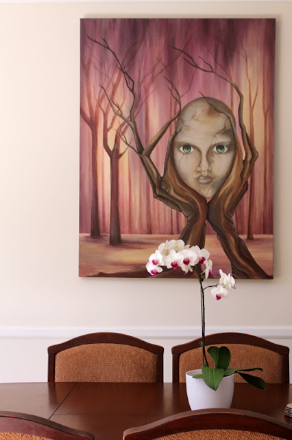 White moth orchid on a table with a painted art piece on the wall