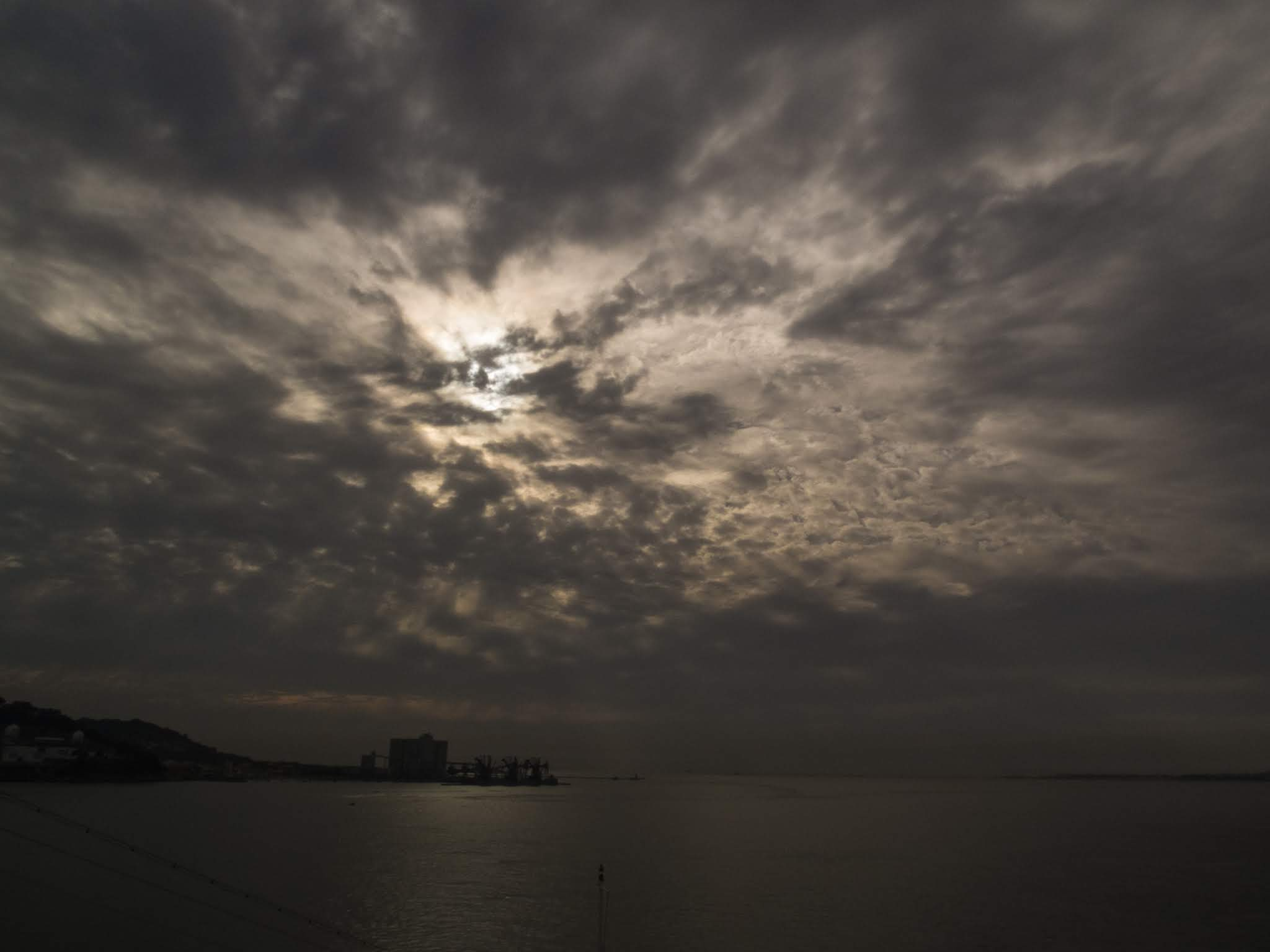 Sun breaking through clouds over an estuary in Lisbon.