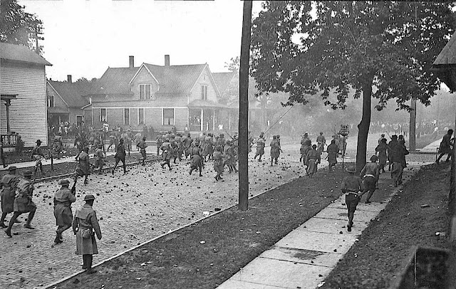 breaking the striking textile workers in 1934 USA, a photograph of charging soldiers in a residential neighborhood