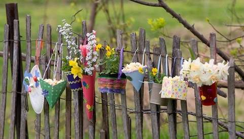 Different types of little flower-filled May Baskets hanging on a grey slatted fence.