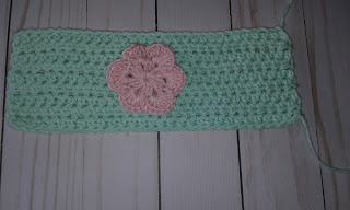 crochet cup sleeve worked flat with a flower applique