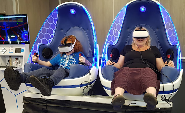 X-Gen VR Review 2 people sitting in egg shaped seats experiencing a  rollercoaster ride
