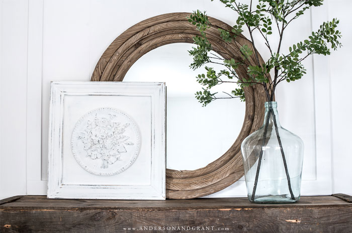 White plaster medallion, demijohn of green branches, and mirror on mantel
