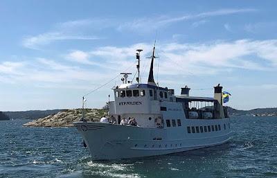 Skärgårdsbåten Byfjorden med passagerare i skärgårdsmiljö.