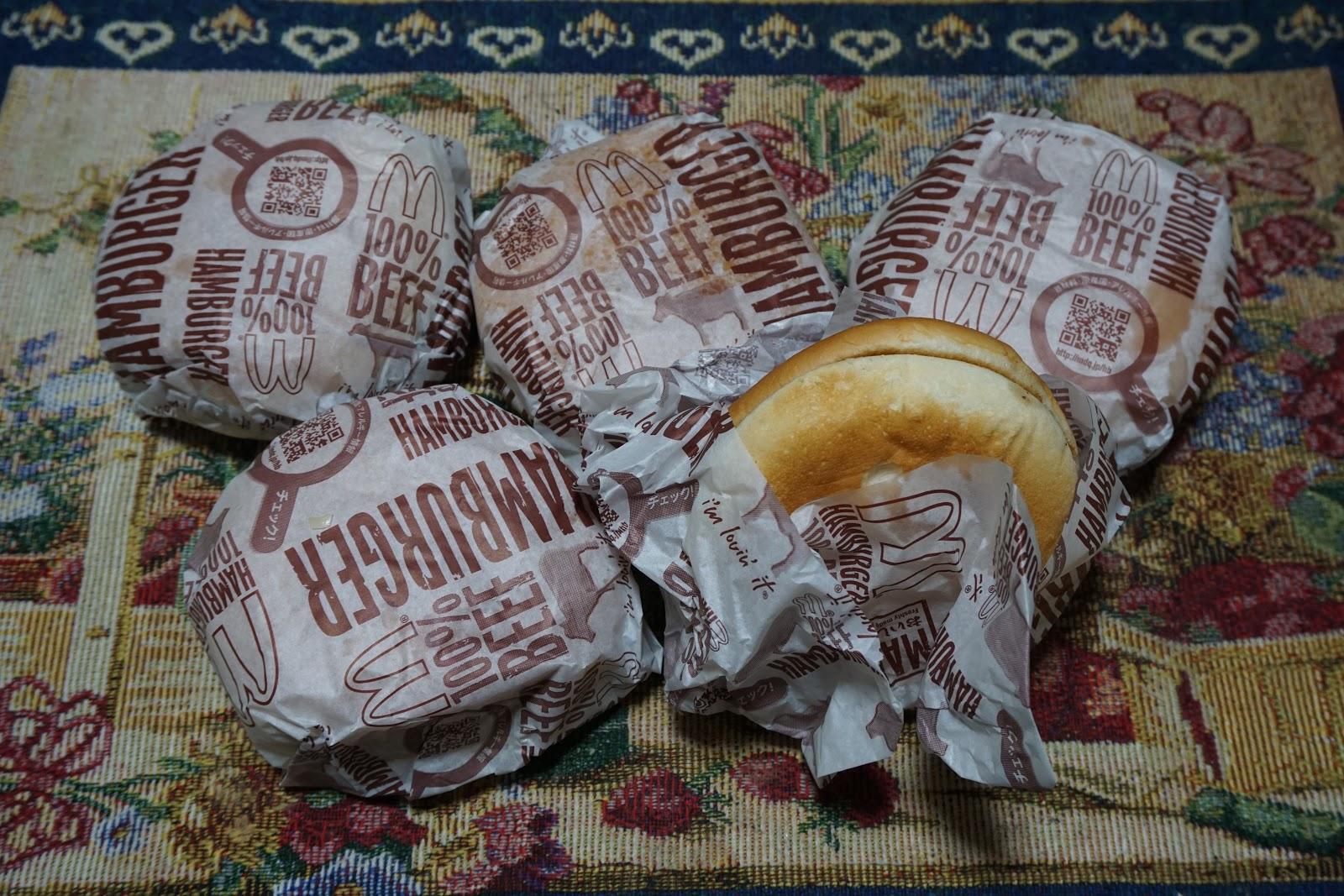 マクドナルドの包装された四つと半分だけ開かれた一つのハンバーガー