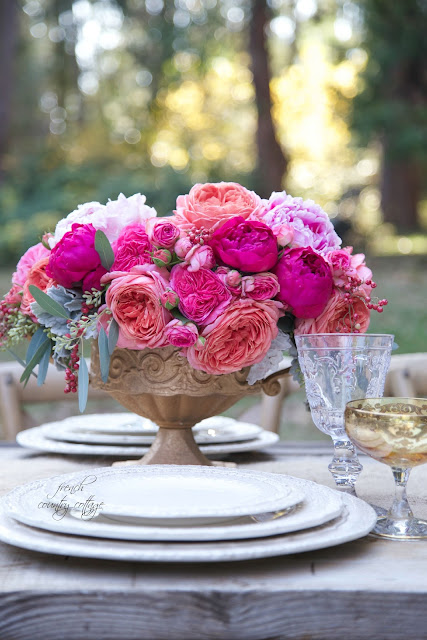 gold container of roses and peonies on table