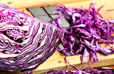 a section of red cabbage next to shredded red cabbage