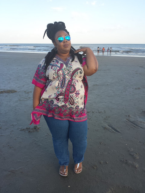 Plus size blogger in paisley print caftan, denim jeans, mirrored aviator sunglasses