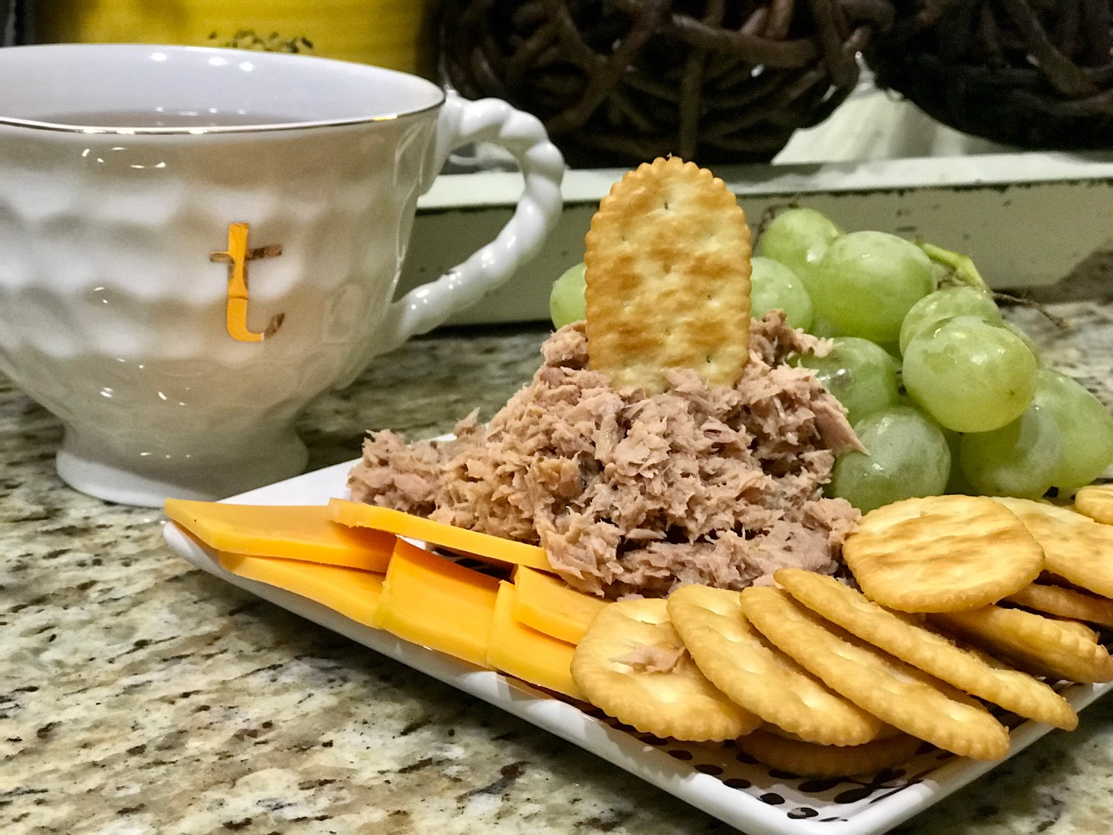 A bit of food on a plate filled with tuna, cheese, crackers and hot tea