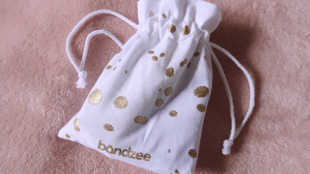 Pink parcel white pouch with gold spots and drawstrings