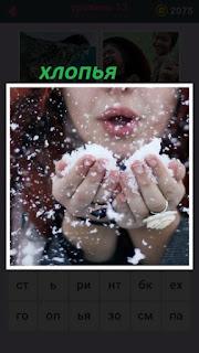 девушка руками держит хлопья снега и дует на них