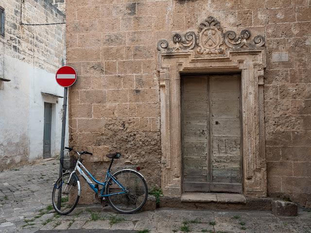 Bicicleta azul frente a fachada barroca con puerta azul y señal de prohibido en Nardó