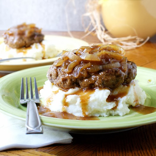 Side view of taditional mashed potatoes under salisbury steak on a green plate.