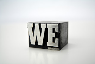 "In block typeset letters, the word ""we"" is in gray metal"