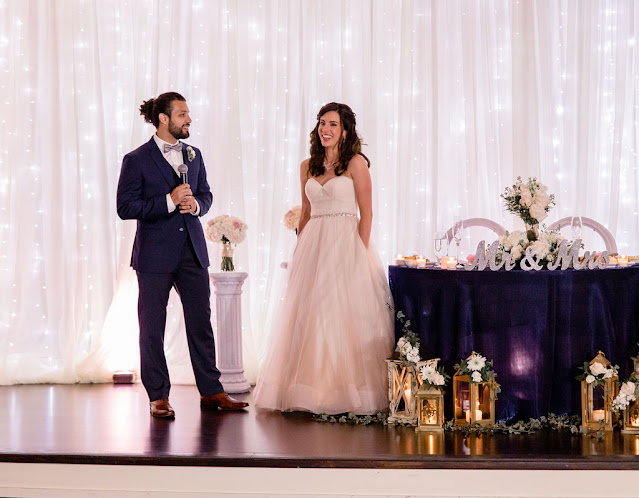 groom toast next to sweetheart table