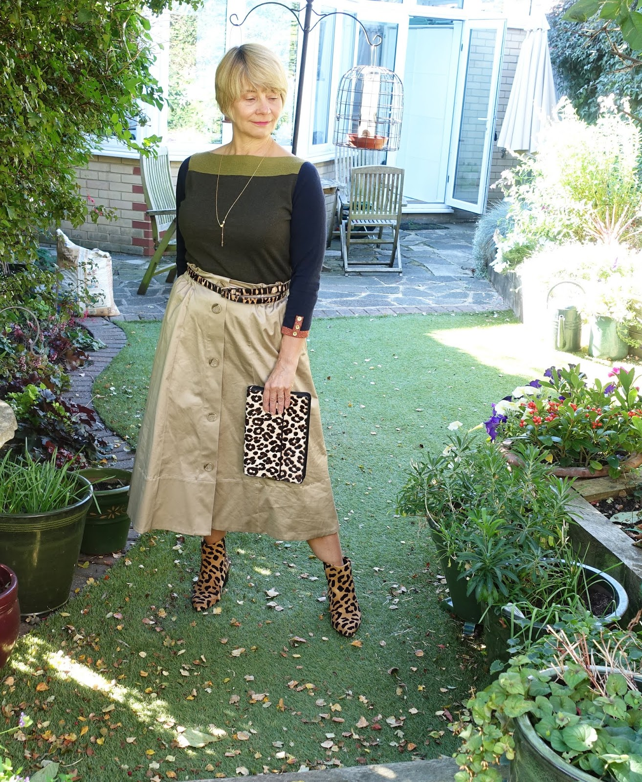 Stylish accessorizing with leopard from Is This Mutton? the blog for the over 45s. Supima camel skirt worn with green and bronze edged jumper with leopard print ankle boots from Office London, leopard clutch and belt from Next.