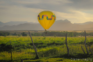 Cramer Imaging's fine art photograph of one yellow rainbow hot air balloon taking flight in Panguitch Utah over a field