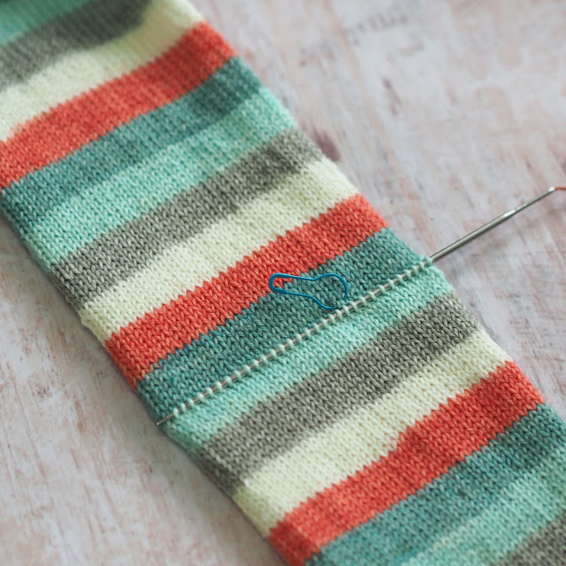 Blue, white and coral sock tube with one needle picking up stitches