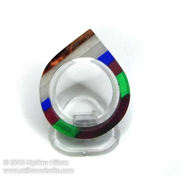 Resin ring featuring stripes of different coloured resin