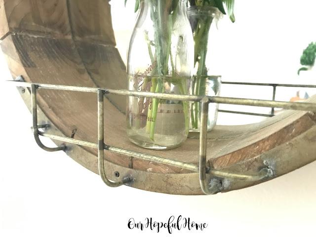 round wooden farmhouse mirror wire cage vintage milk bottle vase fresh cut flowers